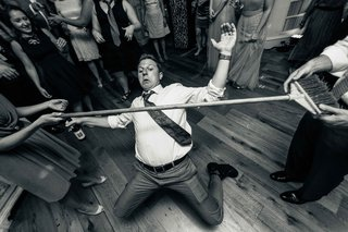 black-and-white-photo-wedding-guests-limbo-at-reception