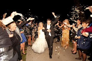 bride-and-groom-walk-through-tunnel-of-guests-with-heart-confetti