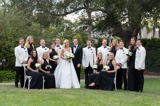bride and groom with bridesmaids in black dresses white bouquets and groomsmen in white tuxedo jackets