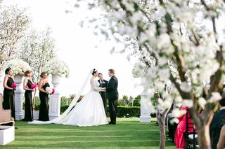 bride-and-groom-at-ceremony-altar-next-to-white-flower-arrangements