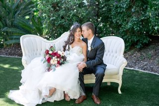 bride-in-alfred-angelo-gown-groom-in-dark-navy-grey-suit-from-the-black-tux-sit-on-fancy-loveseat