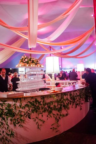 wedding-reception-tent-after-party-lamps-on-bar-with-greenery-purple-violet-pink-lighting-on-drapery