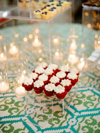 wedding reception dessert table blue green linens red velvet cupcakes with acrylic sign white modern calligraphy candle