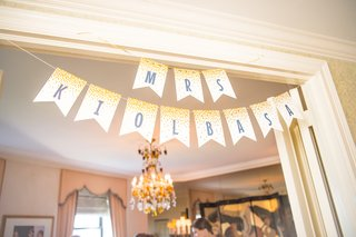mrs-paper-banner-hung-up-in-hotel-suite-while-bride-and-bridesmaids-get-ready-for-wedding