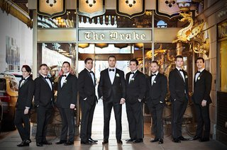 groom-and-groomsmen-pose-in-tuxedos-outside-the-famous-the-drake-hotel-in-chicago