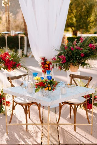 wedding reception courtyard la quinta resort and club marble table wood chairs kumquat pink red yellow flowers