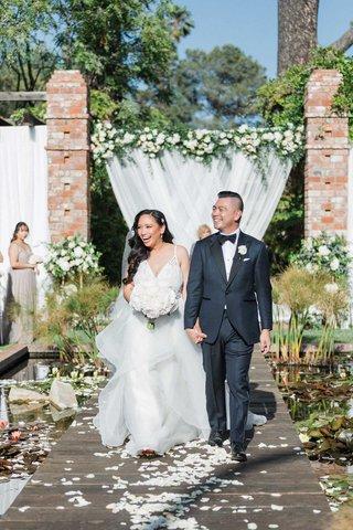 bride-in-v-neck-hayley-paige-wedding-dress-groom-tuxedo-belmond-el-encanto-wood-aisle-lily-pads-pond