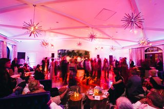 supper-club-theme-wedding-reception-with-guests-on-dance-floor-under-retro-style-light-fixtures