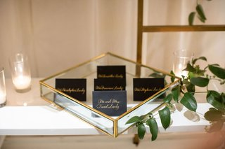 wedding reception bookcase with greenery gold glass tray with black gold script calligraphy escort cards