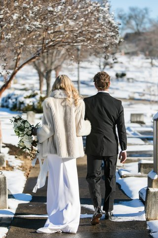 bride-in-gregory-ellenberg-and-fur-coat-arm-in-arm-with-groom-in-brooks-brothers-tuxedo-snow