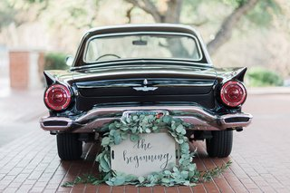 vintage-getaway-car-for-bride-and-groom-with-sign-surrounded-by-greenery-garland
