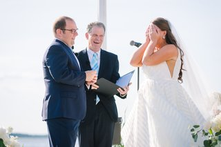 bride-in-striped-hayley-paige-wedding-dress-covers-face-during-ceremony-groom-in-navy-suit
