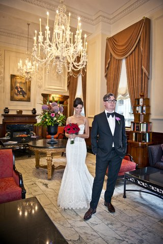 bride-in-pnina-tornai-lace-wedding-dress-approaches-groom-with-glasses-for-first-look