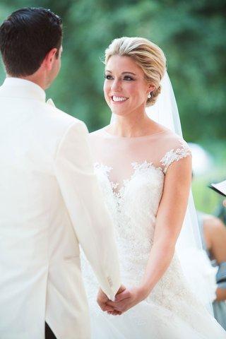 bride-in-illusion-neckline-romona-keveza-ball-gown-wedding-dress-holding-grooms-hand-white-tuxedo