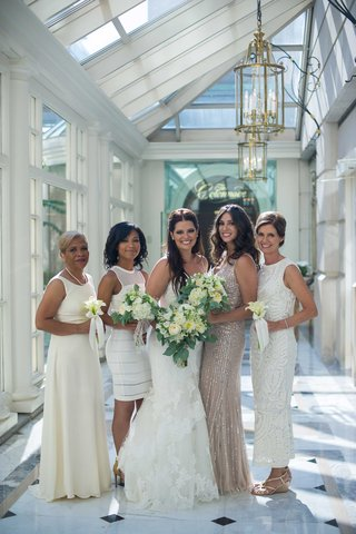 a-bride-in-white-trumpet-gown-bridesmaids-different-white-champagne-dresses-bouquets-foliage