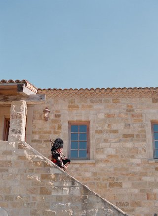 traditional-bagpiper-walking-down-stone-steps