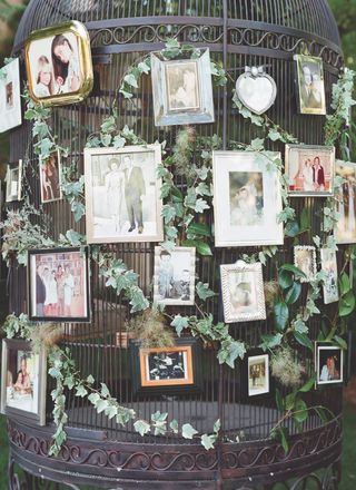 family-photos-displayed-on-a-large-birdcage-for-a-wedding