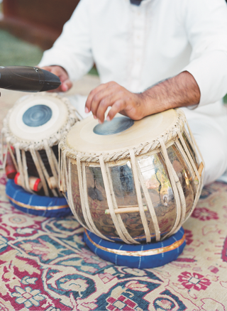 musician-plays-indian-tabla-drums-for-an-outdoor-wedding-ceremony