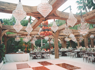 outdoor-wedding-reception-with-crystal-chandeliers-hanging-from-wood-beams