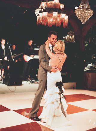 bride-in-a-carolina-herrera-gown-dances-with-a-groom-in-a-grey-tom-ford-suit
