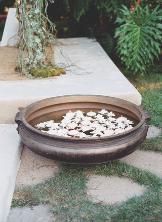 outdoor-wedding-with-indian-uruli-bowls-containing-floating-candles-and-flowers