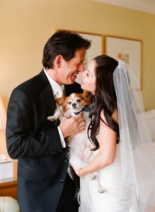 bride-in-a-veil-and-groom-in-a-black-tuxedo-with-dog