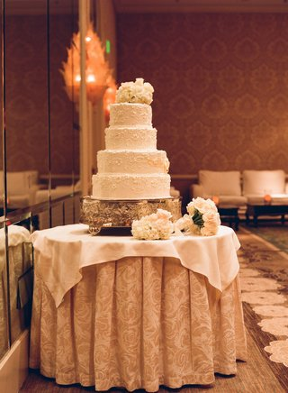 white-wedding-cake-with-a-filigree-pattern-and-topped-with-fresh-white-flowers