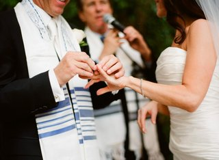groom-places-ring-on-bride-in-a-pronovias-strapless-gown-at-an-outdoor-jewish-ceremony
