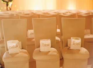 white-paper-bag-with-gold-lettering-on-chairs
