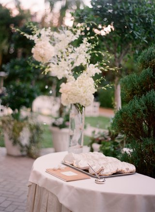 outdoor-jewish-wedding-ceremony-with-a-welcome-table-topped-with-guest-book-and-yarmulke-tray