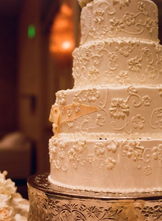 white-wedding-cake-decorated-with-flowers-and-filigree