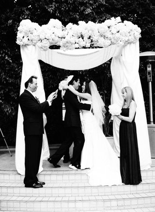 black-and-white-photo-of-bride-and-groom-embracing-at-outdoor-jewish-ceremony