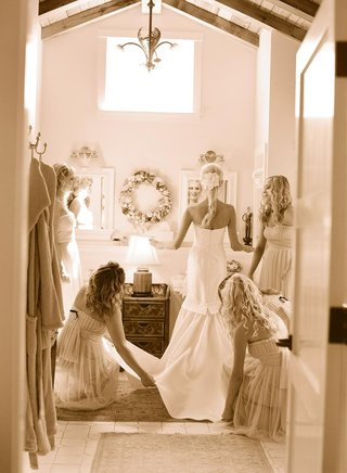 sepia-toned-photo-of-bridesmaids-helping-bride