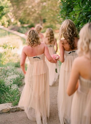bridesmaids-walking-down-path-in-gowns