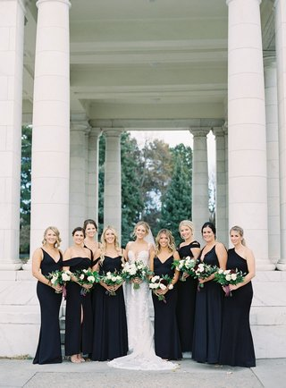 bride-in-berta-wedding-dress-bridesmaids-in-mismatched-black-dresses-gowns-greenery-bouquets