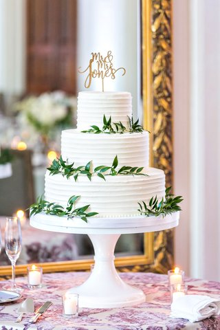 simple-three-layer-wedding-cake-with-white-frosting-greenery-gold-cake-topper-calligraphy-leaves