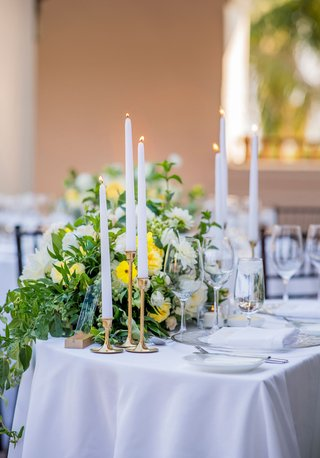wedding-reception-sweetheart-table-taper-candle-gold-candleholder-greenery-white-yellow-flowers