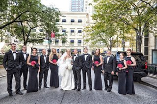 bride-and-groom-with-groomsmen-in-tuxedos-and-bridesmaids-in-black-dresses-with-peplum-detail
