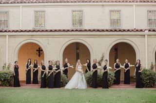 bridesmaids-in-black-dresses-from-aqua-carrying-presentation-bouquet-of-calla-liles