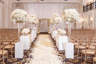 ballroom-wedding-ceremony-gold-chairs-white-risers-flower-arrangements-rose-petal-aisle