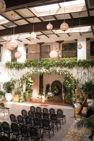 ebell-long-beach-wedding-ceremony-with-orchids-and-greenery-from-balcony-globe-lights-black-chair