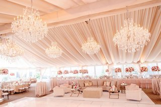 wedding-reception-tent-venue-chandelier-lounge-area-white-pink-flower-centerpiece