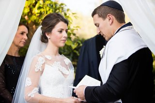 bride-and-groom-with-parents-under-chuppah-at-ceremony-white-sheer-blouse-floral-lace-groom-tallit