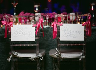 bride-and-groom-wedding-chair-signs-tied-to-clear-chiavari-chairs-with-pink-ribbon