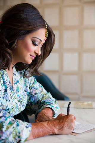 indian-wedding-bride-with-henna-on-hands-writing-note-to-groom-on-wedding-day-in-floral-print-robe