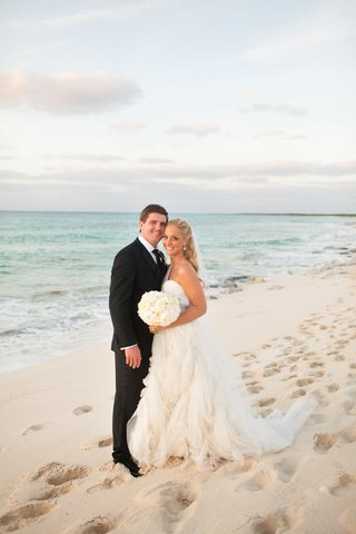 bride-and-groom-stand-in-sand-in-front-of-ocean