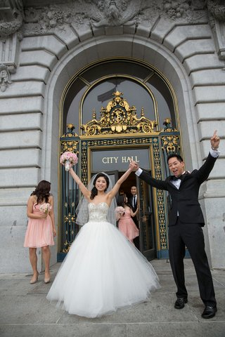 bride-in-kenneth-pool-ball-gown-and-groom-in-tuxedo-with-hands-in-air-at-san-francisco-city-hall