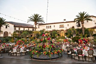 outdoor-wedding-reception-colorful-flowers-spanish-fountain-with-greenery-and-pink-orange-flowers
