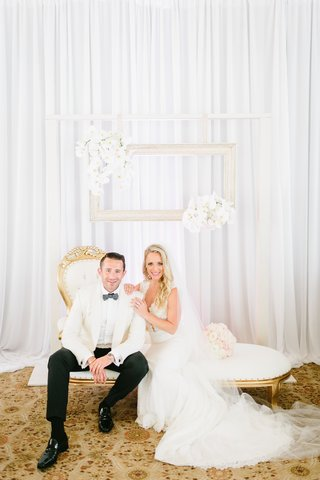 bride-in-ines-di-santo-gown-groom-in-white-tuxedo-jacket-gold-and-white-chaise-lounge-with-frames