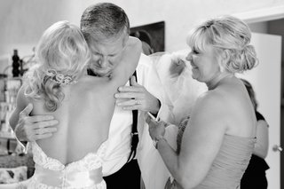black-and-white-photo-bride-hugs-father-of-bride-as-mother-of-bride-watches